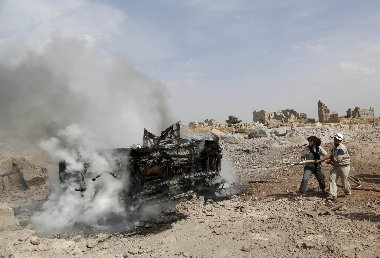 Insurgentes apagam as chamas em um carro bombardeado pelos russos em Idleb, na Síria.