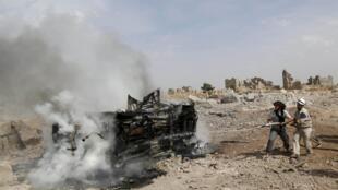 Insurgentes apagan las llamas en un tanque bombardeado por las fuerzas rusas en la localidad siria de Idleb.