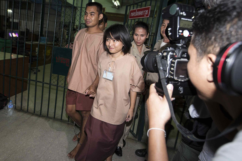 Los estudiantes Patiwat Saraiyaem (centro) y Porntip Mankong (izquierda) abandonan la Corte en asuntos criminales de Bangkok, luego de haber sido condenados por lesa majestad, el 23 de febrero de 2015.