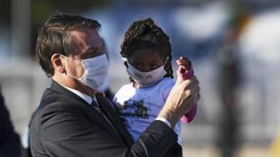 El presidente brasileño Jair Bolsonaro con una niña en brazos, en mayo de 2020 en Brasilia