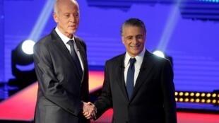 Les candidats à la présidence Kaïs Saïed (à gauche) et Nabil Karoui se saluent avant le débat télévisé de plus de deux heures, vendredi 11 octobre 2019.