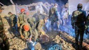 En Ganyá, equipos de rescate tratan de encontrar supervivientes entre los escombros y reunían restos humanos en bolsas mortuorias negras.