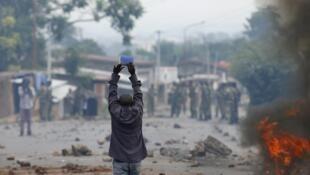 Un manifestant brandit une bible lors des affrontements avec la police, mercredi 20 mai à Bujumbura.