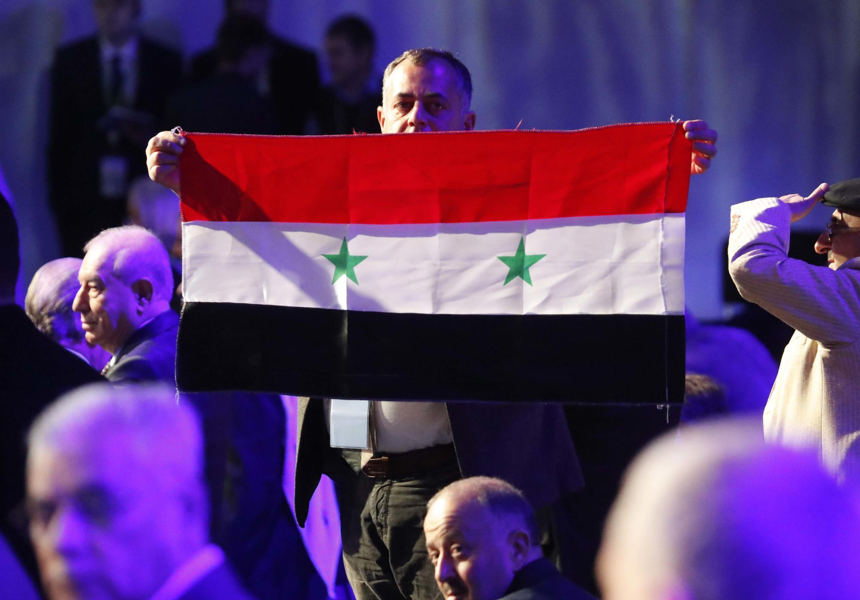 Một người tham dự Đại hội đối thoại quốc gia giương cờ Syria, tại Sotchi, Nga, ngày 03/01/2018