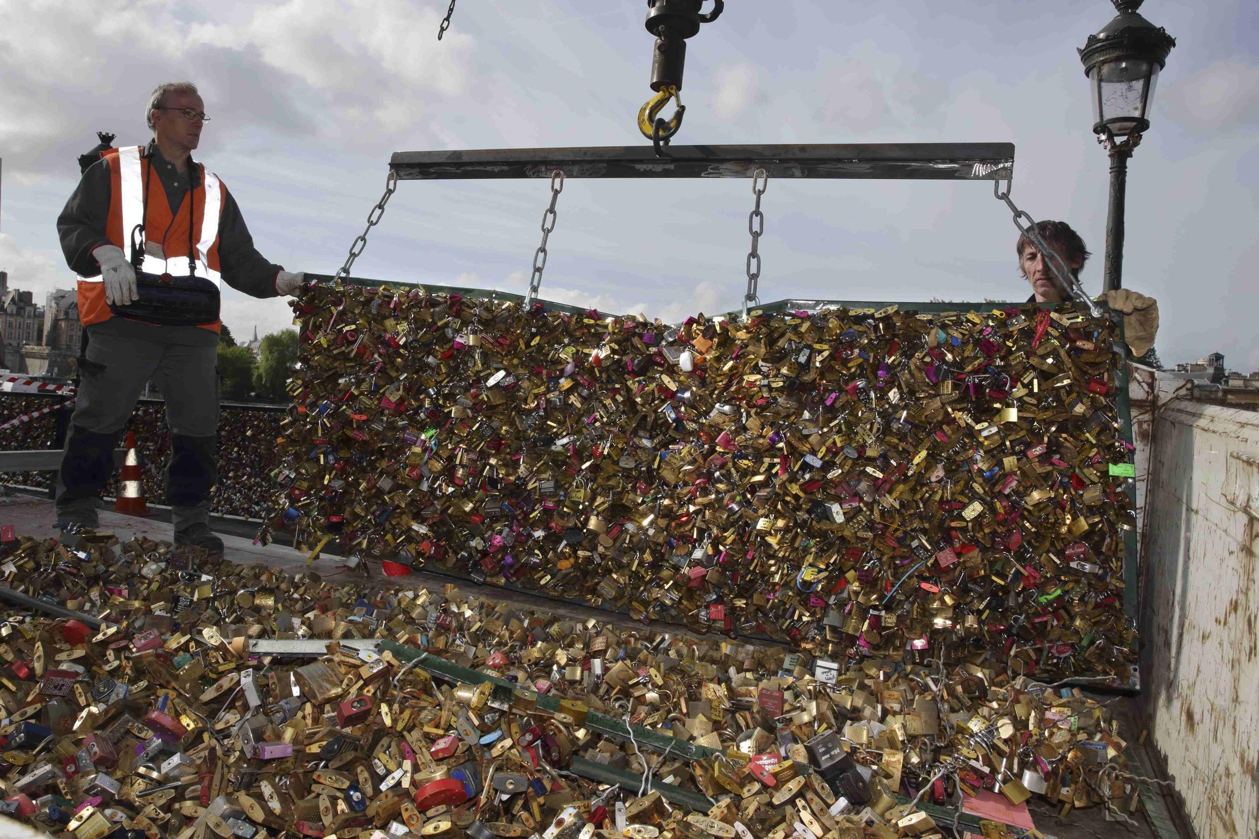 """City municipal employees lower iron grills covered with """"love locks"""" into a truck after they were removed from the Pont des Arts in Paris, France, June 1, 2015"""