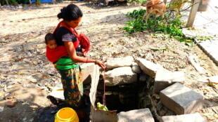 Sharada devant le puits insalubre où elle puise de l'eau.