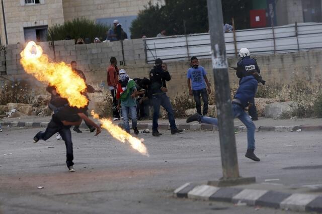 Um manifestante palestino joga um coquetel molotov na direção das forças israelenses durante comemoração do Nakba em Ramallah nesta quarta-feira, 15 de maio de 2013.