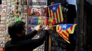 """Un comerciante pone la bandera separatista catalana, llamada """"estelada"""" en Barcelona, el 22 de diciembre de 2017."""