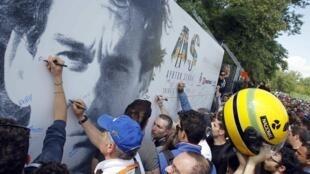 Fãs de Ayrton Senna assinam outdoor com a imagem do piloto, na cerimônia em homenagem aos 20 anos da morte do brasileiro no circuito de Ímola.