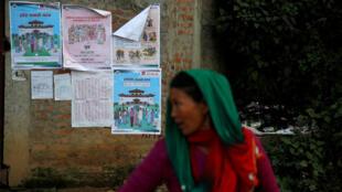 Une femme passe près d'un bureau de vote à Chautara, dans le district de SIndhupalchok, le 25 novembre 2017, à la veille des élections.