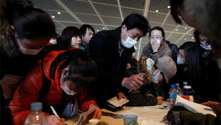 Chinese citizens register at a desk at Narita airport, set-up by China's embassy, to help them leave Tokyo
