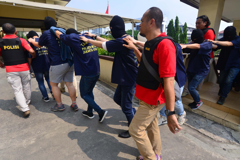 Police indonésienne escortant un groupe d'hommes suspectés d'homosexualité et arrêtés lors d'un raid, le 22 mai 2017.