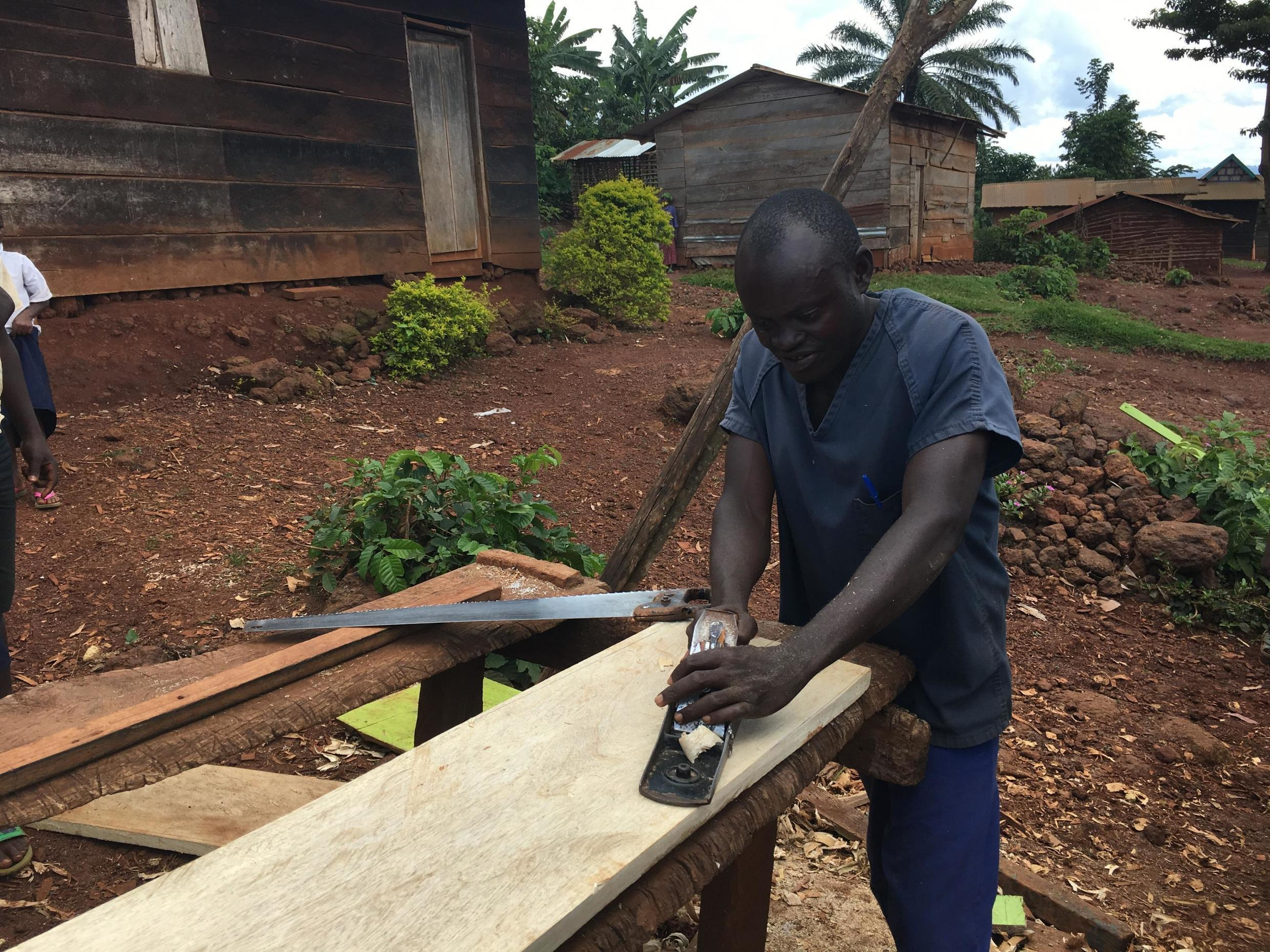 Carpenter Sombi Hassani works outside his atelier in Bingo, a small town in North Kivu, DRC