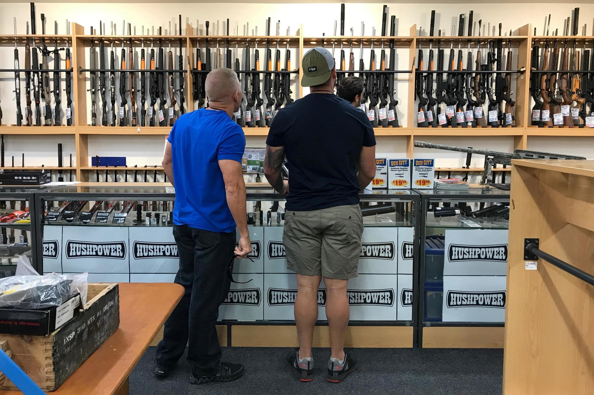 People look at firearms and accessories on display at Gun City gunshop in Christchurch, New Zealand