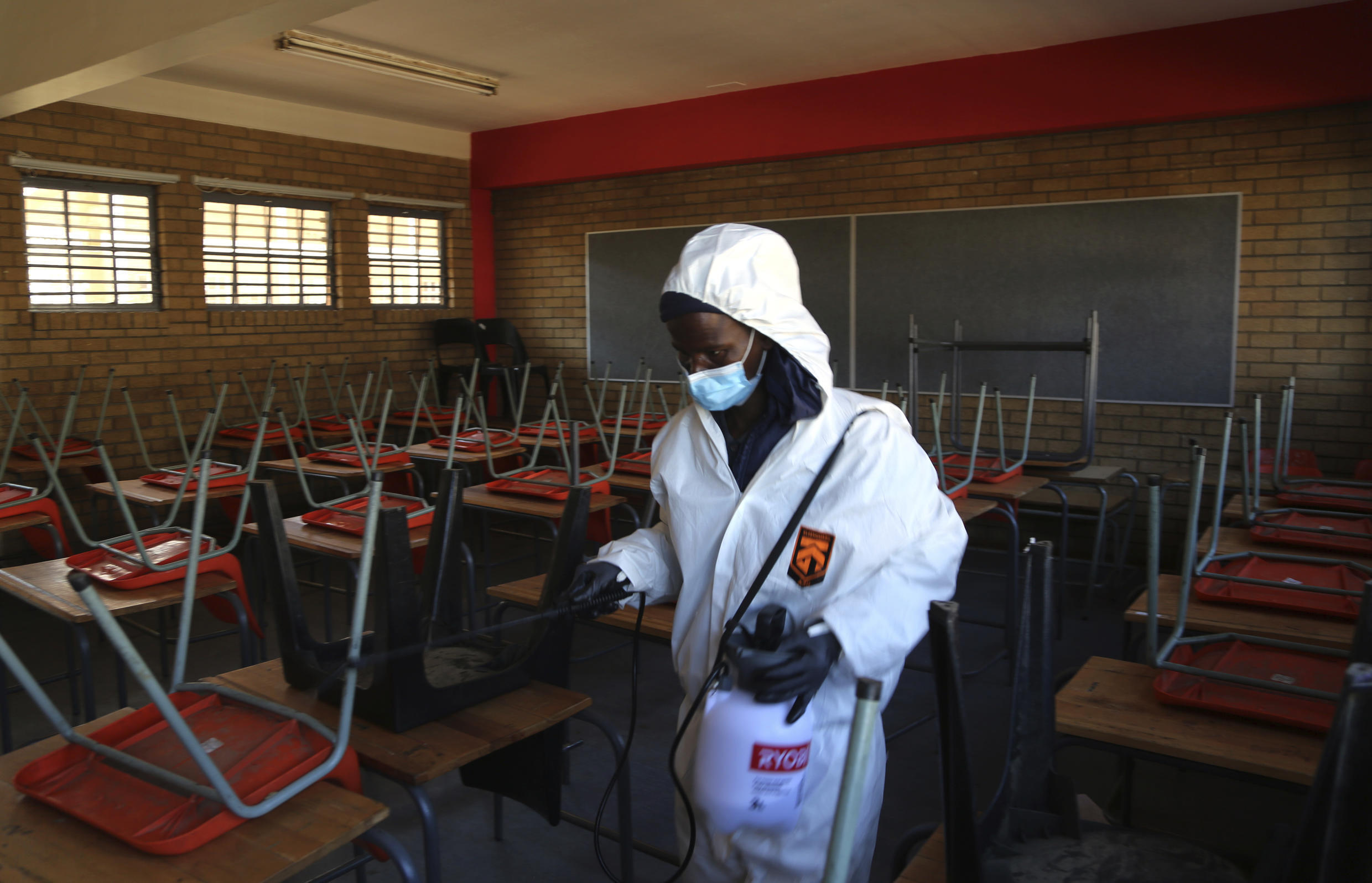 A cleaner sprays disinfectant in a classroom to help reduce the spread of Covid-19 ahead of the reopening of Landulwazi Comprehensive School, east of Johannesburg, South Africa.