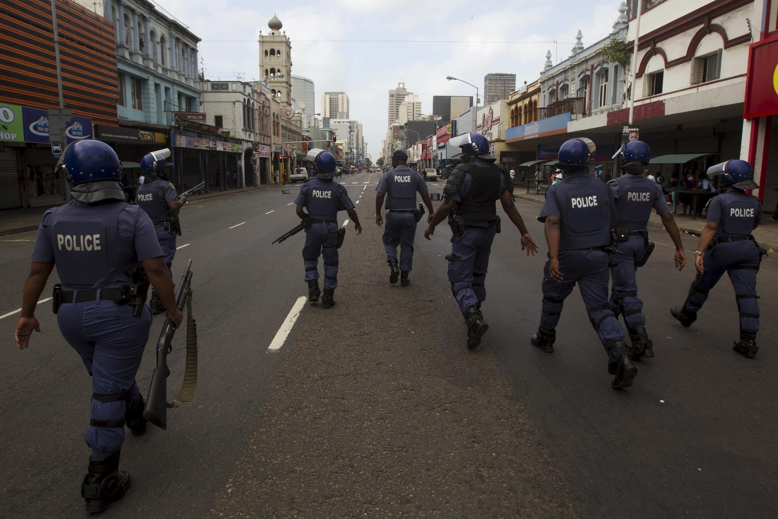 Police clear the streets in an attempt to quell rioting and looting caused by xenophobic violence in Durban 14 April 2015