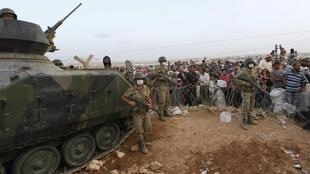 A Turkish tank meets refugees at the border with Syria