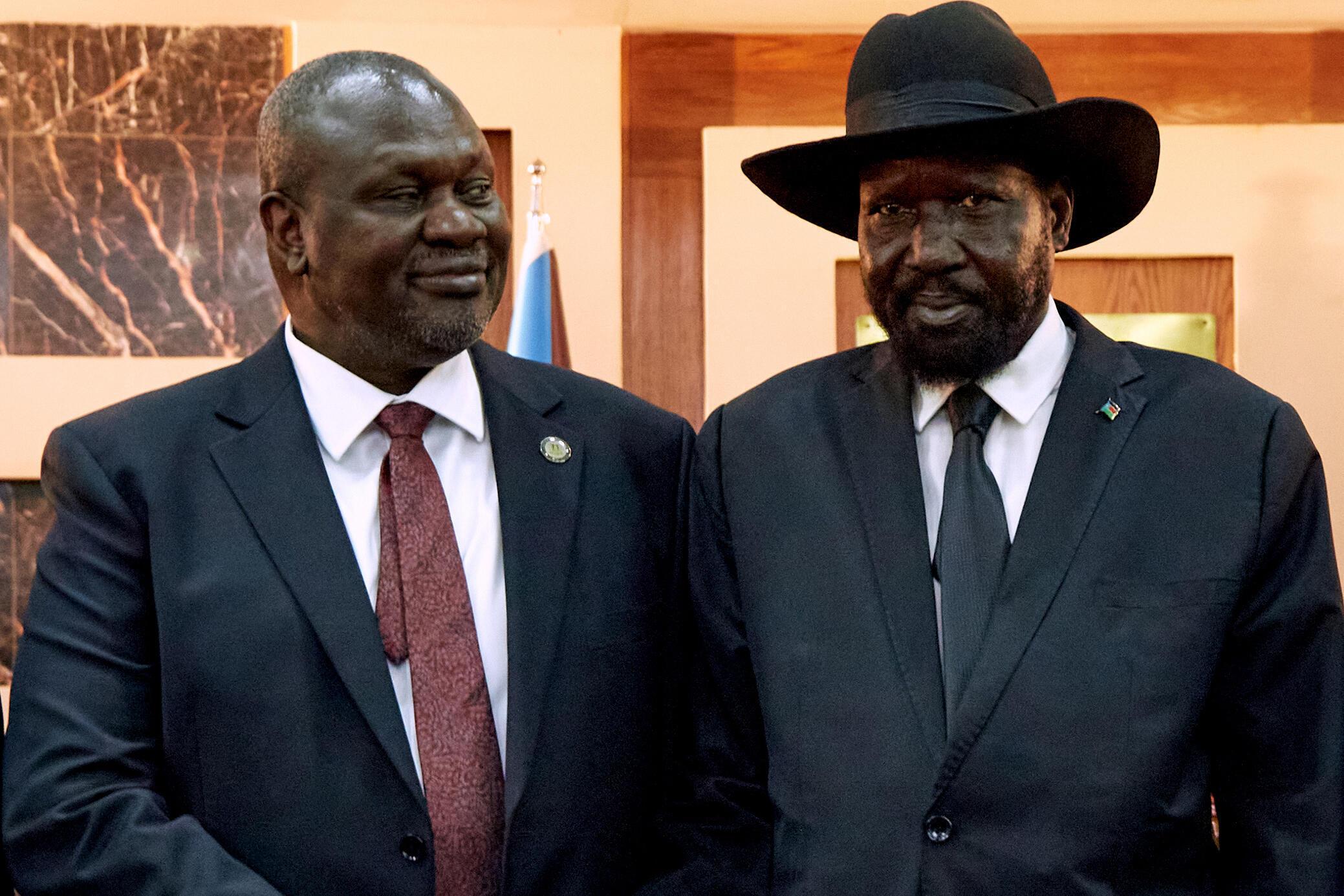 South Sudanese President Salva Kiir (R) shakes hands with First Vice President Riek Machar in 2020