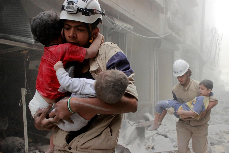 Maafisa wa idara ya uokoaji wakiokoa watoto baada ya shambulio la anga lililotekelezwa na vikosi vinavyotii serikali ya Syria katika kitongoji cha al-Shaar cha Aleppo, Juni 2, 2014.