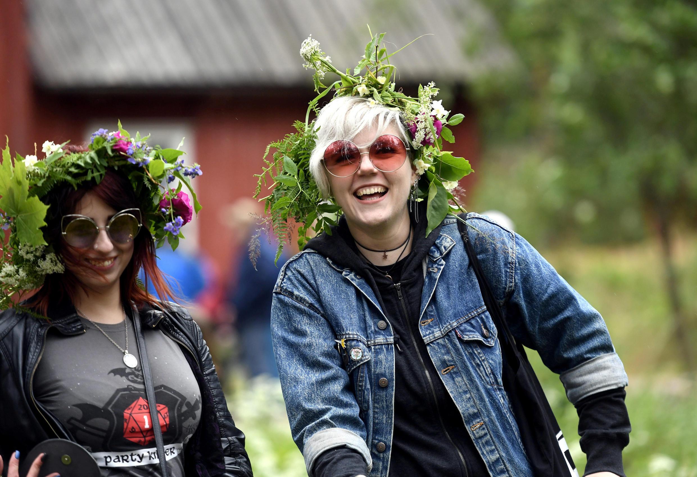 Mulheres com coroas de flores comemoram o solstício de verão no museu ao ar livre de Seurasaari em Helsinque, Finlândia, em 22 de junho de 2018.