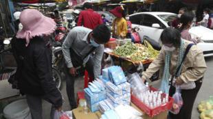 Sur un marché local de Phnom Penh, des Cambodgiens achètent des masques pour contenir la propagation du Covid-19, le 10 avril 2021.