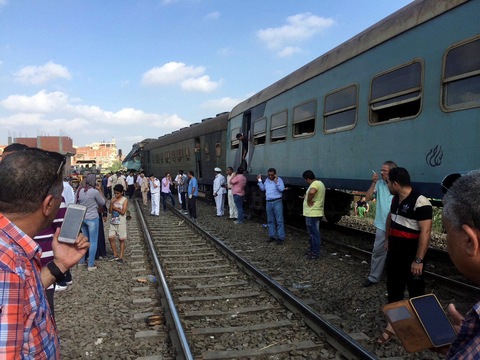 Des égyptiens observent les trains rentrés en collision près de la station de Khorshid, à Alexandrie, le 11 août 2017.