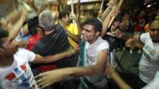 Des immigrés vivant en Grèce tentent d'en calmer d'autres, après qu'une dispute a éclaté entre un immigré et un homme au cours d'une manifestation antiraciste à Nikaia.