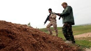 Un peshmerga, acompañado por un oficial de la coalición, durante una sesión de entrenamiento en la región de Arbil, norte de Irak, 24 de marzo de 2015.