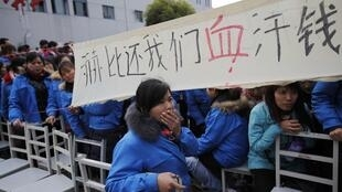Trabalhadores se manifestam na entrada da fábrica da Hi-P International em Xangai, no dia 5 de dezembro.