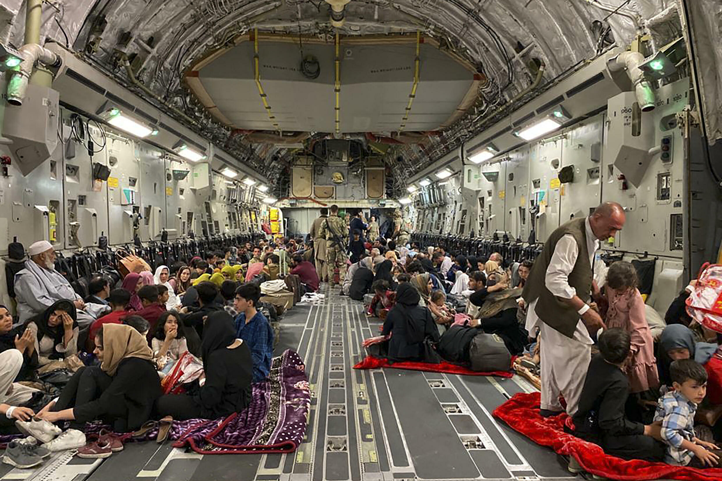Afghans sit inside a US military aircraft as they prepare to leave Afghanistan at the military airport in Kabul