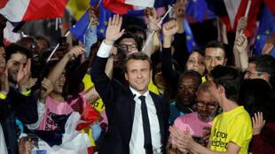 Emmanuel Macron acena para o público em comício nesta segunda-feira