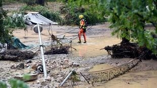 A rescuer stands in a flooded and damaged area of a camping site in Saint-Julien-de-Peyrolas, France on August 9, 2018.
