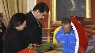Le président Nicolas Maduro, sa femme Cilia Flores, et le président de l'Assemblée nationale Diosdado Cabello autour du cercueil du député Robert Serra, le 2 octobre 2014 à Caracas.