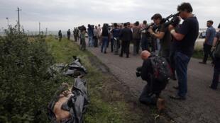 بازرسان بینالمللی و کارشناسان سازمان امنیت و همکاری اروپا در محل سقوط هواپیمای مالزیایی.