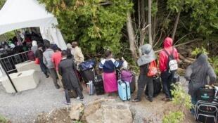 Vérifications d'identité, le 6 août 2017, sous une grande tente dressée au bout d'un chemin forestier, principal point d'entrée des migrants dans le sud du Québec.