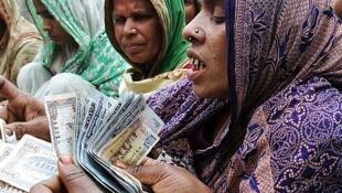 Des femmes comptent l'argent pour le remboursement d'un microcrédit au village de Dowtia, près de Dhaka au Bangladesh.