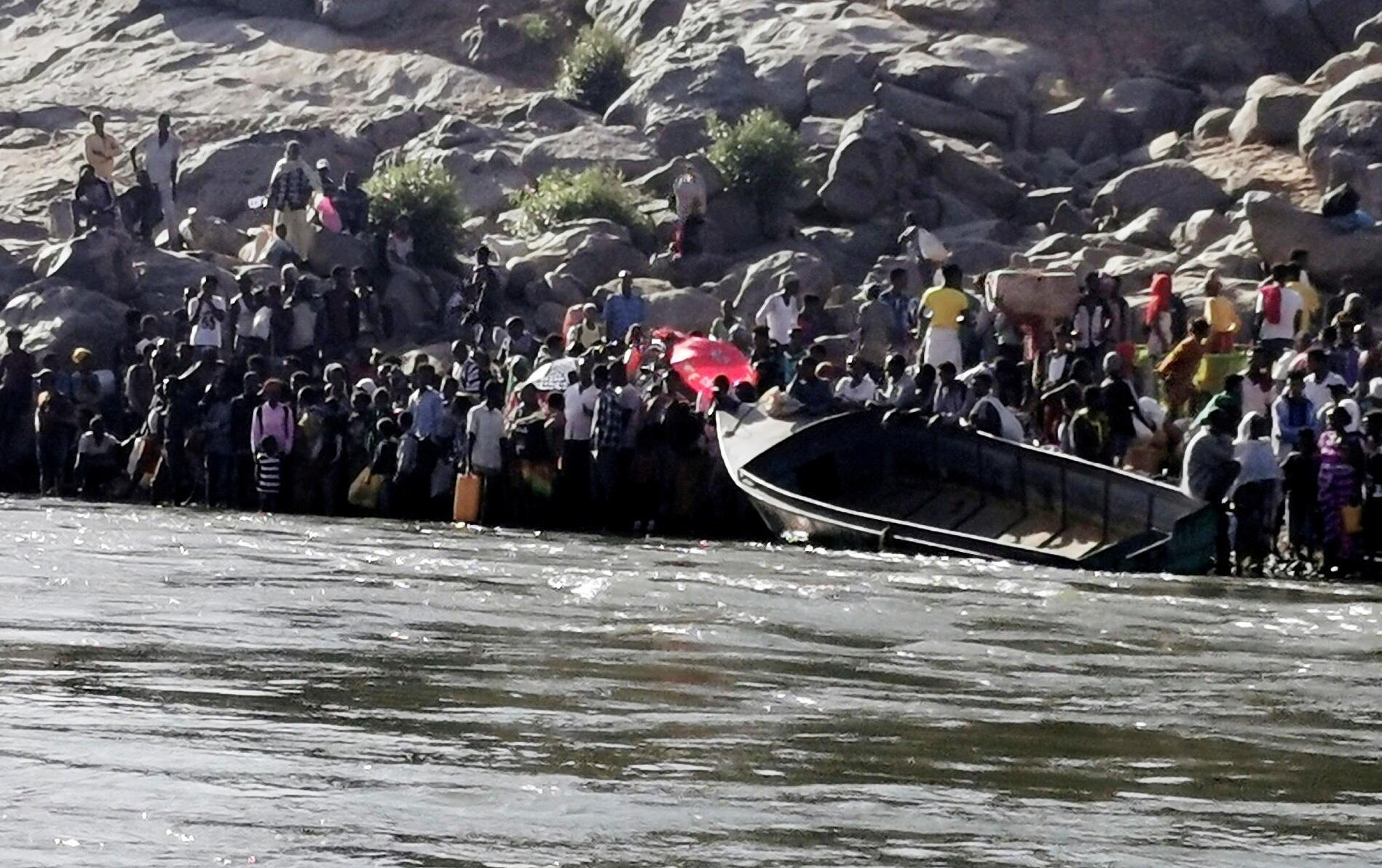 Des Éthiopiens fuyant les combats au Tigré se préparent à traverser la rivière Setit qui marque la frontière entre l'Éthiopie et le Soudan, au niveau du village d'Hamdayet, dans l'État de Kassala.
