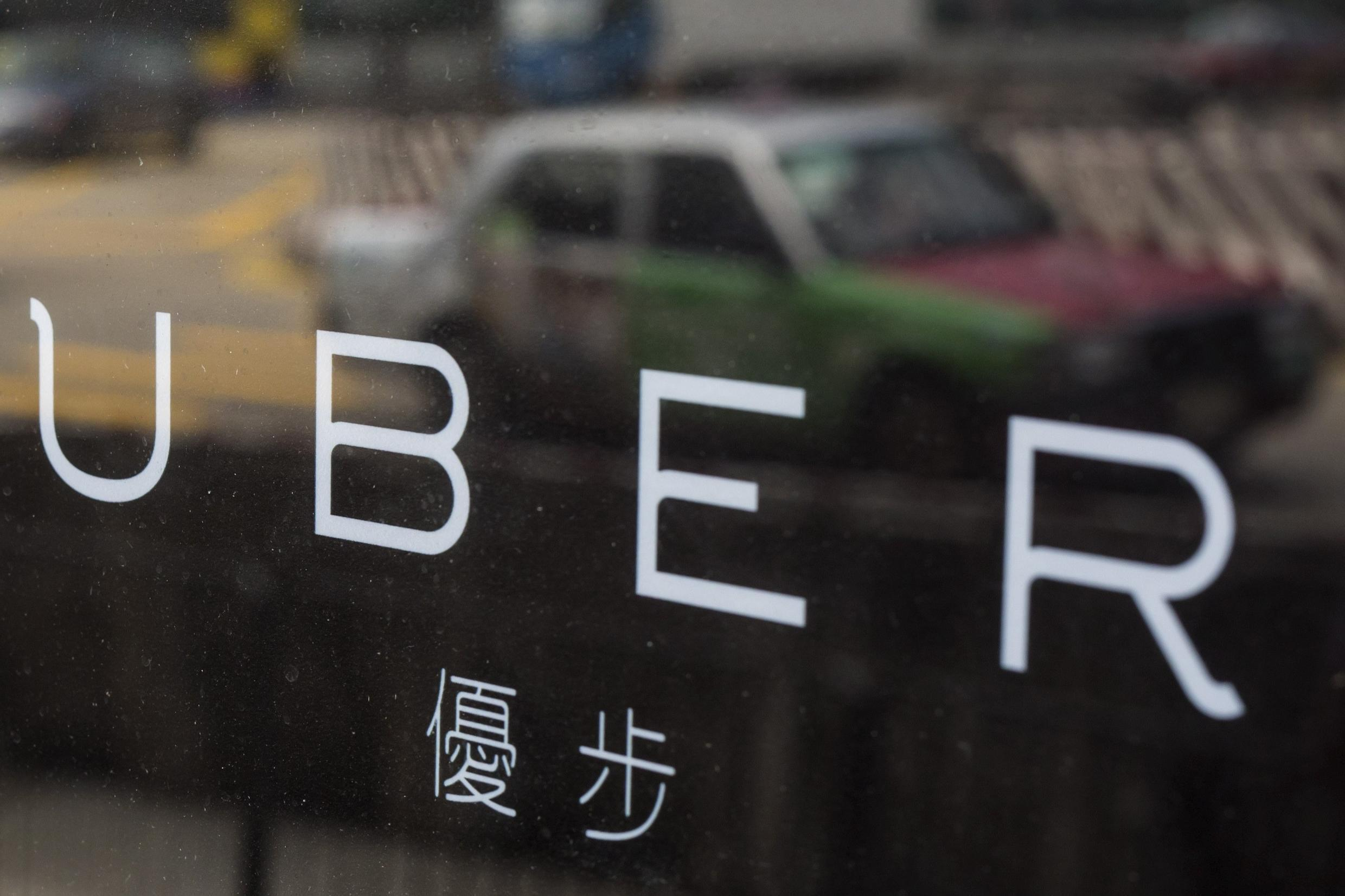 A taxi is reflected in a window at an Uber office in Hong Kong