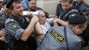 Garry Kasparov (vestido de branco) sendo preso quando manifestava contra a condenação do grupo punk Pussy Riot, na sexta-feira, em Moscou.