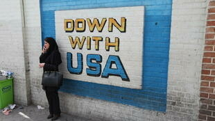 A woman standing next to an anti-US slogan painted at the former US embassy in Tehran.