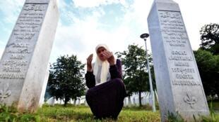 Una superviviente musulmana de la masacre de Srebrenica reza ante las tumbas de sus dos hijos en el cementerio de Potocari, en Bosnia, el 10 de julio de 2020