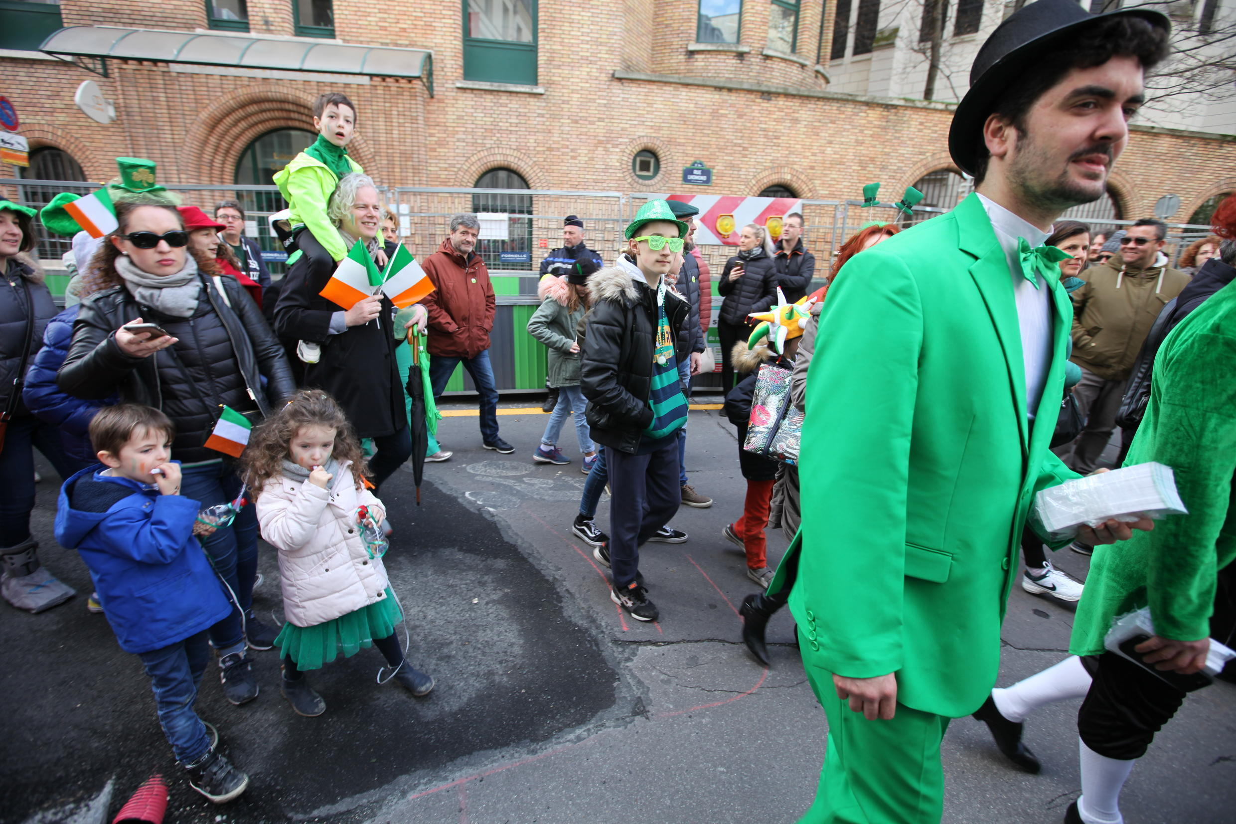 Young and old, dressed up in green, carry the Irish flag.