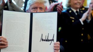 """Donald Trump se declaró """"orgulloso"""" mostrando su firma sobre el veto presidencial."""