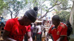 Des vendeurs ambulants de Dakar remontent leur étal, démoli quelques jours plus tôt lors d'une opération de déguerpissement menée par la police.
