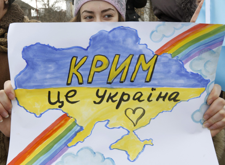 """""""Crimeia é Ucrânia"""", diz cartaz de uma manifestante anti-guerra na Crimeia."""
