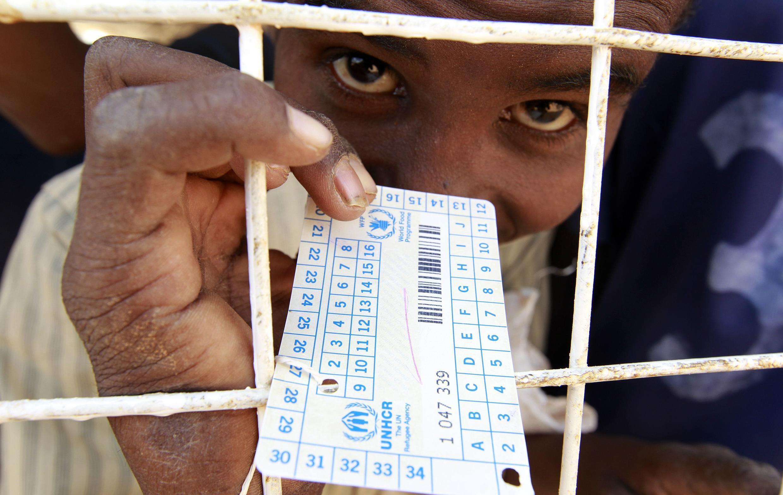 A refugee displays his food ration card near the Kenya-Somalia border