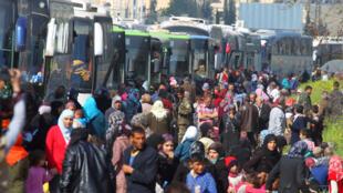 Sírios que foram retirados das cidades de Kefraya e al-Foua ao lado dos ônibus que os transportaram em 15 de abril de 2017.