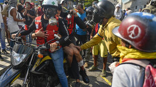 An injured anti-government protester is taken away in a motorcycle after clashing with security forces during the commemoration of May Day in Caracas on May 1, 2019.