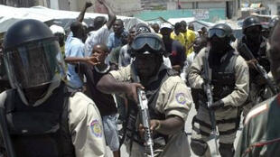 Police walk between residents taking part in a protest in Port-au-Prince on 11 May 2010