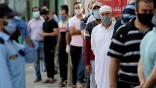 À Gaza, le le 1er septembre, des fonctionnaires palestiniens attendent de recevoir leurs salaires devant une banque lors du confinement décrété le 25 août dans le territoire.